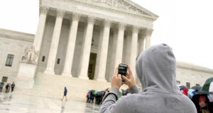 A Supreme Court visitor uses his cellphone to take a photo of the court in Washington.  (AP Photo, File)