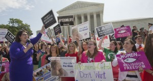 Kristin Hughs, left, cheers on with supporters  of the Supreme Court's decision on the Hobby Lobby case June 30. The Supreme Court says corporations can hold religious objections that allow them to opt out of the new health law requirement that they cover contraceptives for women. (AP photo: Pablo Martinez Monsivais)