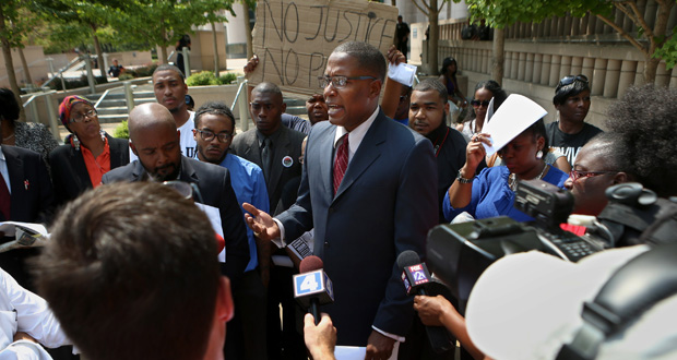 Malik Z. Shabazz, president and founder of Black Lawyers for Justice based in Washington, D.C., holds a news conference in front of the federal courthouse in St. Louis where he announced the details of a $40 million lawsuit his organization filed against police and the governments of Ferguson and St. Louis County. (AP photo)