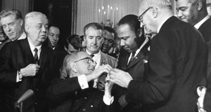 The Rev. Martin Luther King, third from right, was among national figures present on July 2, 1964, as President Lyndon B. Johnson signed the Civil Rights Act. Thirteen months later, Johnson signed the Voting Rights Act. (AP file photo)