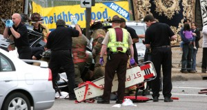 In this June 10, 2006, photo, Koua Fong Lee, back right, holding is 4-year-old daughter, with his wife, Panghoua Moua, looks on as emergency personnel work at the scene of an accident after the 1996 Camry he was driving rear-ended an Oldsmobile at high speed in St. Paul. (AP file photo: St. Paul Pioneer Press)
