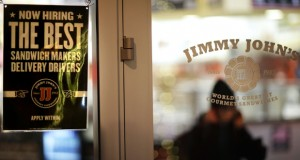 A sign advertises job opportunities at a Jimmy John's sandwich shop as an employee walks out to make a delivery on Friday, Jan. 2, in Atlanta. (AP photo)