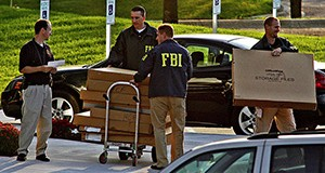 In this Sept. 24, 2008, file photo, FBI agents haul boxes of unknown items from the Petters Group headquarters building in Minnetonka. (AP file photo: Star Tribune)