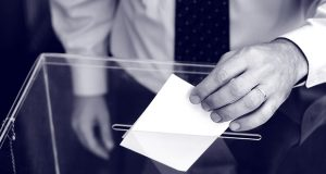 Hand of a person putting a ballot into voting box.