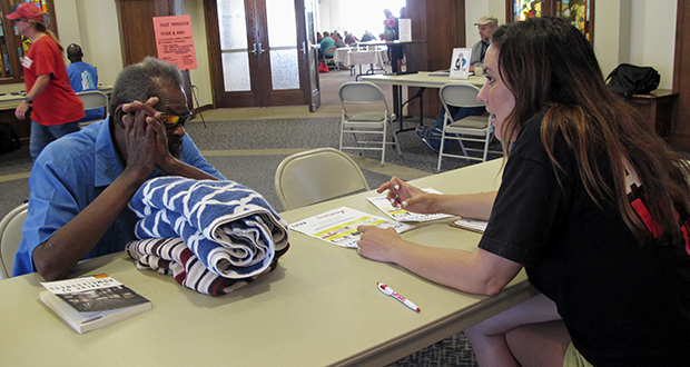 In this Aug. 31 photo, Molly McGrath, who works for VoteRiders to help people get the required photo identification needed to vote, assists Mike Battles with questions about early voting in Madison, Wisconsin. (AP file photo)