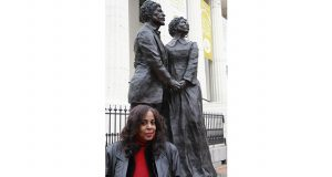 Lynne Jackson, the great-great-granddaughter of Dred and Harriet Scott and founder of the Dred Scott Heritage Foundation, stands in front of a life-size sculpture of Dred and Harriet Scott at the Old Courthouse in downtown St. Louis.