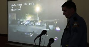 St. Paul Police Sgt. Mike Ernster is silhouetted as a dash cam video shows the June 24 confrontation between officers, a police dog and Frank Baker. The video was played before Police Chief Todd Axtell addressed the media during a news conference Nov. 4. The city has agreed to pay Baker $2 million. (AP file photo: Jim Mone)