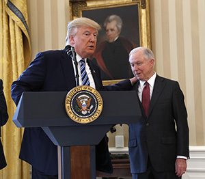 President Donald Trump talks to Attorney General Jeff Sessions in the Oval Office of the White House on Feb. 9 before Vice President Mike Pence administered the oath of office for Sessions. (AP photo)