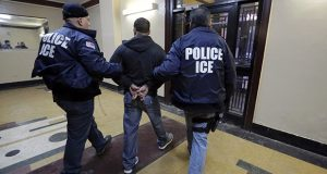 In this March 2015 photo, Immigration and Customs Enforcement officers escort an arrestee in an apartment building in the Bronx borough of New York. (AP file photo)