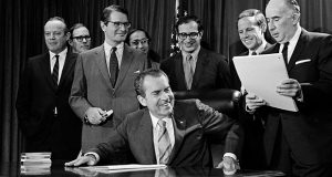 """President Richard M. Nixon turns to Attorney General John Mitchell, right, after signing a drug bill in Washington in 1970. The next year, Nixon told Mitchell, """"I don't think a woman should be in any government job whatever."""" (AP file photo)"""
