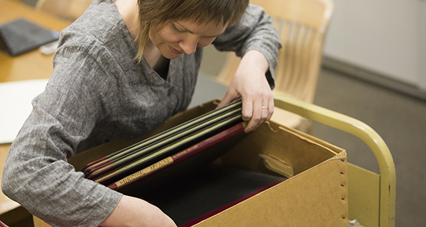Ellen Jaquette, reference librarian at the Minnesota Historical Society, frequently helps lawyer research bills' legislative intent. Ancient committee books, like those shown here, are a primary tool. (Staff photo: Kevin Featherly)