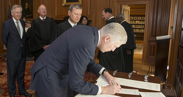 In this photo provided by the U.S. Supreme Court's public information office, Chief Justice John Roberts Jr. and fellow justices watch as Neil Gorsuch signs the constitutional oath Monday at the Supreme Court in Washington. (AP photo)