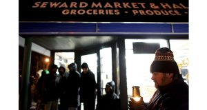 Neighbor Stephen Benjaminson holds a lantern outside the Seward Market and Halal Meat in Minneapolis on Jan. 7, 2010, as members of the local Somali community gather in front of the store to hold a vigil after three men were shot and killed during a robbery there. The Minnesota Supreme Court upheld three consecutive life sentences for Mahdi Hassan Ali, who was convicted in the killings. (AP file photo: Star Tribune)