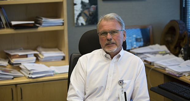 Minnesota Corrections Commissioner Tom Roy sits in his St. Paul office, surrounded by the studies and reports that are the grist of his data-driven approach to the job. (Staff photo: Kevin Featherly)