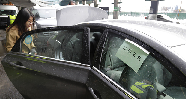 A woman gets in an Uber car March 15 at LaGuardia Airport in New York. The company faces conflicts with customers who say they have been hurt by drivers, and drivers who say they have been hurt by customers. (AP file photo: Seth Wenig)