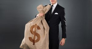 Midsection of businessman carrying sack with dollar sign against gray background