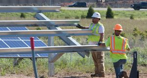 A crew works at a solar panel project at Interstate 35 and Franklin Road in Norman, Oklahoma. The state ranks among the top 10 for solar energy potential. (BridgeTower Media photo: Brent Fuchs)