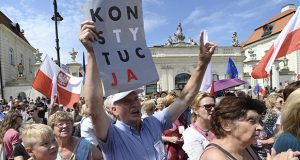 People shout slogans Monday in front of the presidential palace in Warsaw, Poland. Polish President Andrzej Duda vetoed two contentious bills widely seen as assaults on the independence of the judicial system. (AP Photo)