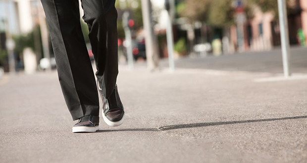 Person Walks in a Suit and Sneakers