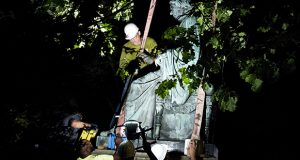 Workers remove a monument dedicated to U.S. Supreme Court Chief Justice Roger Brooke Taney from outside the Maryland State House, in Annapolis, Md., early Friday, Aug. 18. The statue of the U.S. Supreme Court justice who wrote the 1857 Dred Scott decision was lifted away by a crane about 2 a.m. It was lowered into a truck and driven away to storage. (AP photo)