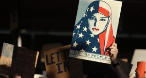 In this Jan. 28 file photo a protester holds a sign at San Francisco International Airport during a demonstration to denounce President Donald Trump's first executive order barring citizens of seven predominantly Muslim-majority countries from entering the U.S. (AP file photo)