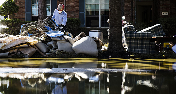 Homeowner Sohail Soomro dumps flood-damaged debris on his front yard in the aftermath of Hurricane Harvey on Thursday at the Canyon Gate community in Katy, Texas. (AP photo)
