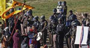 A person with a hand drum paces between law enforcement officers and a line of oil pipeline protesters south of St. Anthony, North Dakota, on Monday, Oct. 10, 2016. (AP photo: The Bismarck Tribune)