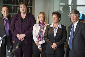 Former University of Minnesota Duluth women's hockey coach Shannon Miller, second from right, former UMD women's basketball coach Annette Wiles, second from left, and former UMD women's softball coach Jen Banford, center, attend a news conference Sept. 28, 2015, about the discrimination lawsuit they filed against the school. Lawyers Donald Mark Jr., right, and Dan Siegel, left, look on. (AP photo: Star Tribune)
