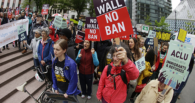 Protesters wave signs and chant during a May 15 demonstration against President Donald Trump's revised travel ban outside a federal courthouse in Seattle. The U.S. Supreme Court's decision allowing Trump's third travel ban to take effect, at least for now, has intensified the attention on a legal showdown before three 9th U.S. Circuit Court of Appeals judges in Seattle who have previously been cool to the administration's efforts. (AP file photo)