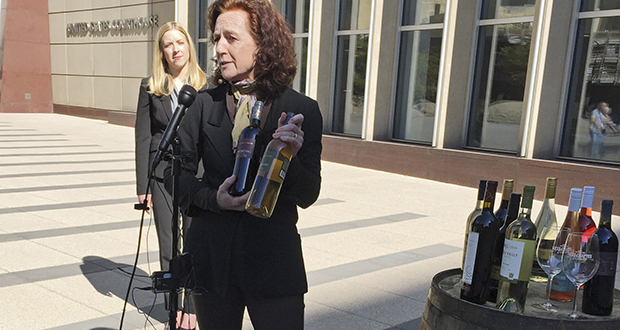 Nan Bailly, owner of Alexis Bailly Vineyard of Hastings, Minnesota, with attorney Meagan Forbes in the background, holds bottles of wine from her winery at a news conference March 28, 2017, outside the federal courthouse in Minneapolis. (AP file photo)