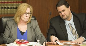 Sen./Lt. Gov. Michelle Fischbach, R-Paynesville, reaches for a folder at the start of a Jan. 9 meeting of the Legislative Task Force on Child Protection, a bicameral body on which she serves as the Senate's co-chair. Committee administrator Jason Fossum sits to her left. (Staff photo: Kevin Featherly )
