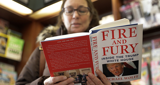 """Kathy Mallin, of Glenview, Illinois, looks over a copy of """"Fire and Fury: Inside the Trump White House"""" by Michael Wolff on Jan. 5 at Barbara's Books Store. (AP photo)"""
