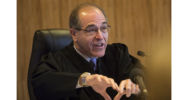 In effect, Judge John H. Guthmann's ruling says that Sauk Center DFL activist Destiny Dusosky lacks standing to bring a lawsuit seeking Michelle Fischbach's removal from the state Senate and that the court lacks jurisdiction to decide it, at least as things now stand. Guthmann is shown presiding over a hearing in the case Feb. 6. (AP pool photo: Star Tribune)