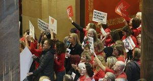 Supporters of Moms Demand Action, a group advocating stricter gun laws, rally outside the Minnesota House Chamber on Tuesday in St. Paul. They called on lawmakers to expand background checks and resist efforts to ease the state's existing gun laws after the school shooting in Florida last week that killed 17 students and teachers. (AP photo: Jim Mone)