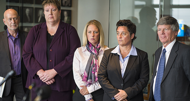 Former University of Minnesota Duluth women's hockey coach Shannon Miller, second from right, former UMD women's basketball coach Annette Wiles, second from left, and former UMD women's softball coach Jen Banford, center, attend a news conference Sept. 28, 2015, about the discrimination lawsuit they filed against the school. Lawyers Donald Mark Jr., right, and Dan Siegel, left, look on. (AP file photo: Star Tribune)
