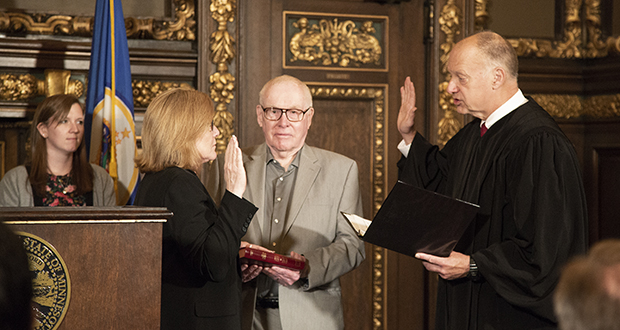 Michelle Fischbach takes the oath of office as lieutenant governor at the Capitol on Friday from Supreme Court Associate Justice G. Barry Anderson. Fischbach, who resigned from the Minnesota Senate earlier in the day, said she will not run in a special election to fill her vacated Senate seat. She also said that a lawsuit to oust her from the Senate in a dispute over her dual roles will be voluntarily withdrawn by the plaintiff Friday afternoon. Fischbach remained Senate president after ascending to lieutenant governor in January when Tina Smith left that post to become a U.S. senator. Fischbach's father, Tom St. Martin, holds the Bible during Friday's ceremony.  (Staff photo: Kevin Featherly)