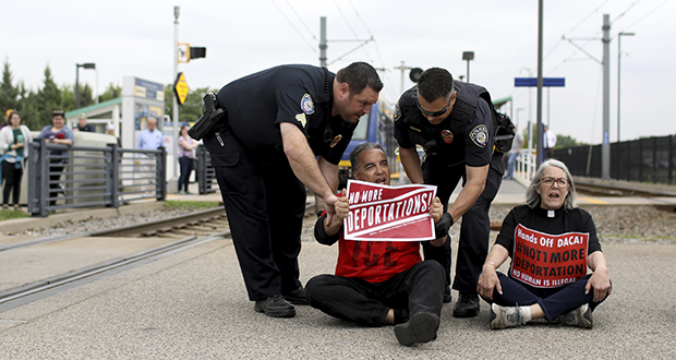 Police officers arrest the Rev. Daniel Romero, of the First Congregational Church of Minnesota, after Romero and several other protesters blocked light rail tracks at the Fort Snelling Station on May 22, 2018. (AP photo: Star Tribune)