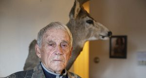 """A determined former DFL Sen. Bob Lessard, candidate for state attorney general at age 87, poses with one of the two mounted deer displayed in his St. Paul apartment. The """"Old Trapper"""" says he would sue the Legislature to protect Legacy Amendment funds. (Staff photo: Kevin Featherly)"""