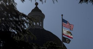 Trump administration deregulators plan to challenge to California's ability to set its own car-pollution limits, according to people familiar with the deliberations. In this photo, the American, California and POW/MIA flags fly in front of the California State Capitol building in Sacramento. (Bloomberg file photo)