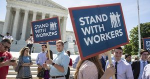 In this June 25 photo, people gather at the Supreme Court awaiting a decision in an Illinois union dues case, Janus vs. AFSCME, in Washington. (AP file photo)