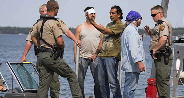 James Northrup, third from right, Todd Thompson, third from left, and Leonard Thompson, second from right, talk with conservation officers at a public dock after having their nets seized from Gull Lake on Aug. 28, 2015, in Nisswa, Minnesota. (AP file photo: Star Tribune)