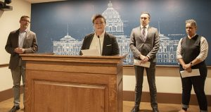 OutFront Minnesota Executive Director Monica Meyer speaks out against GOP attorney general candidate Doug Wardlow at the Capitol on Wednesday. Wardlow has dedicated his career to discrimination, she said. DFL Sen. Scott Dibble (left), former DFL attorney general nominee Matt Pelikan and Stonewall DFL caucus Chair Erica Mauter look on. (Staff photo: Kevin Featherly)