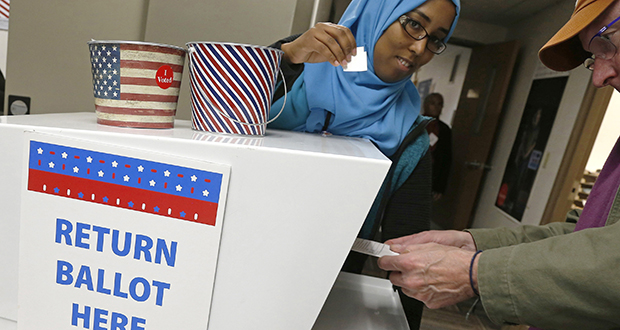 """An election judge, left, has an """"I Voted"""" sticker ready to hand to a voter Oct. 18 as he inserts his ballot into the collection box at an early-voting station in downtown Minneapolis. (AP photo: Jim Mone)"""