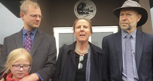 Clearwater County District Judge Robert Tiffany abruptly dismissed charges against three climate change activists during their trial Oct. 9, saying prosecutors failed to prove that the protesters' attempt to shut down two Enbridge Energy oil pipelines caused any damage. In this photo, defendant Emily Johnston, center, speaks outside Clearwater County courthouse in Bagley, Minnesota, with co-defendant Ben Joldersma, left, and his daughter, and former NASA scientist James Hansen. (Minnesota Public Radio via AP)