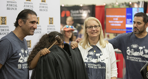 Ramsey County District Court judges G. Tony Atwal (left), Robyn Millenacker and Jeffrey Bryan pose with a girl as she models a judicial robe at the Minnesota State Fair in August. Atwal lost his seat on the bench to P. Paul Yang in Tuesday's election. (File photo: Kevin Featherly)