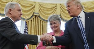 Happier days: President Donald Trump shakes hands with Attorney General Jeff Sessions, accompanied by his wife, Mary, after Sessions was sworn-in on Feb. 9, 2017. (AP file photo)