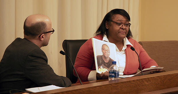 Sa'Lesha Beeks, right, holds a photo of her slain mother, Birdell Beeks, while testifying for House File 8 on Feb. 27. The bill's author, Rep. Dave Pinto, DFL-St. Paul, looks on. (Staff photo: Kevin Featherly)