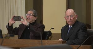 Just before presenting House File 2128, his bill to reintroduce a state parole board to Minnesota, Rep. Carlos Mariani, DFL-St. Paul, has a bit of fun with his camera phone. Corrections Commissioner Paul Schnell is also pictured. (Staff photo: Kevin Featherly)
