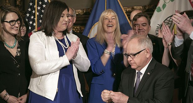 Jenny Teeson, wearing pearls at left, applauds after Gov. Tim Walz signed into law a bill, which Teeson championed, that does away with the marital rape exception. Standing between Teeson and the governor is Tesson's mom, Terri Teeson. (Staff photo: Kevin Featherly)