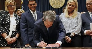 Georgia's Gov. Brian Kemp, center, signs legislation May 7 banning abortions once a fetal heartbeat can be detected. (AP PHOTO)